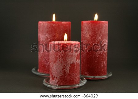 Set of three candles against black background - stock photo