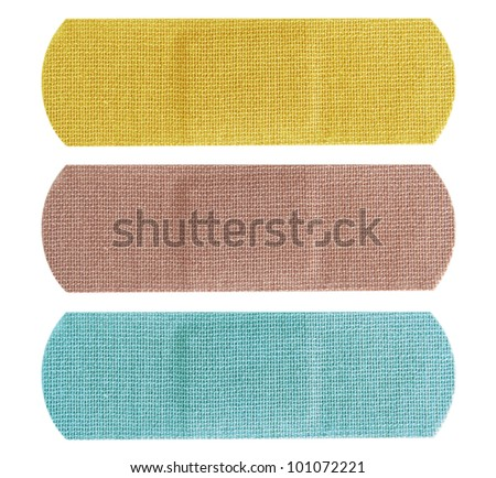 Set of three colored bandaids or bandages in blue, yellow and beige over white. - stock photo