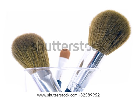 Set of three makeup brushes for face powder, concealer and eye shadow, in a glass. Isolated on white background.