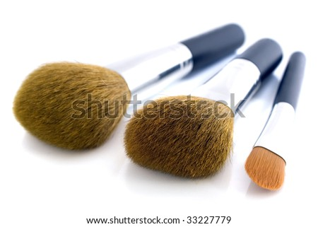 Set of three makeup brushes for face powder, concealer and eye shadow. Isolated on white background. - stock photo