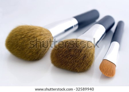 Set of three makeup brushes for face powder, concealer and eye shadow, on white background.