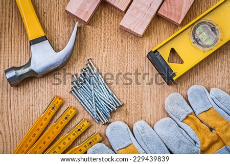 set of tools claw hammer stack of nails safety gloves construction level wooden meter planks on wooden board - stock photo