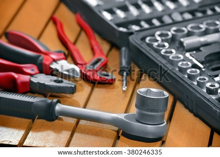 set of tools for repair in a case on a wooden table, screwdriver,  pliers, drills, pliers, repair, low depth of field - stock photo