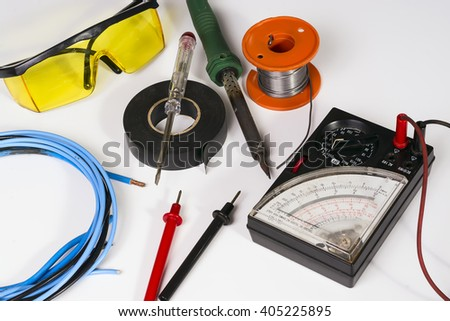 Set of tools used by an electrician. There is a voltmeter, soldering iron, wires, goggle, screwdriver, insulating tape and solder. Everything is arranged on a white surface. - stock photo