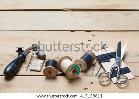 Set of tools with cutter, scissors, needle, thread spools for home made embroidery, needlework and tailoring, on wooden background.