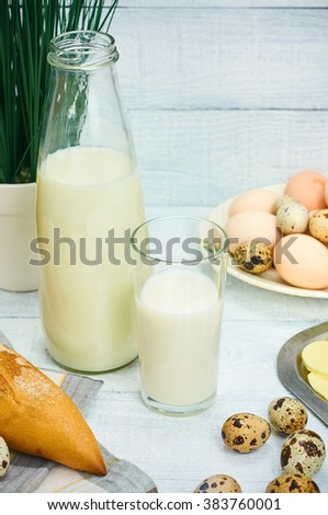 Set of traditional countryside breakfast. Milk bottle, glass, eggs, butter and bread over white wooden background. Selective focus