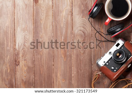 Set of travel and resort stuff. Camera, headphones and coffee cup on wooden table. Top view with copy space - stock photo