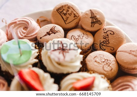 Set of travel macaroons in beige color with french inscriptions, Eiffel tower and Paris on the plate