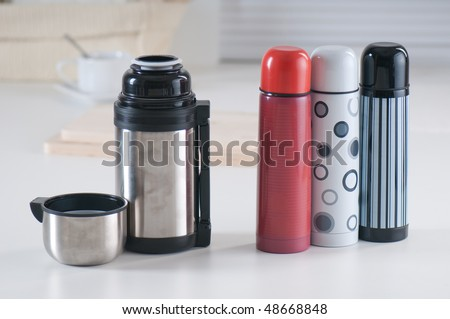 Set of vacuum flasks on a kitchen table - stock photo
