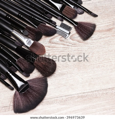 Set of various makeup brushes: for applying foundation, powder, blush, eyeshadow, eyebrow brushes, fan brush and others. Professional tools of make-up artist on shabby wooden surface. Copy space - stock photo