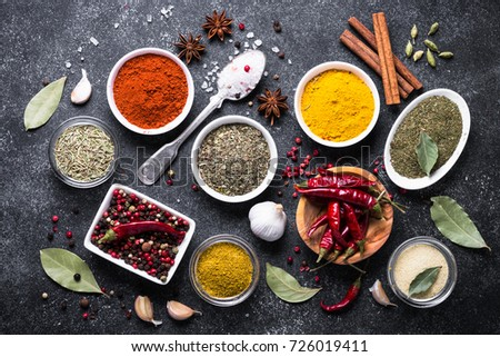 Set of Various spices on black stone table. Chilly pepper, rosemary, basil, turmeric, paprika, garlic, anise, cinnamon and other. Top view.