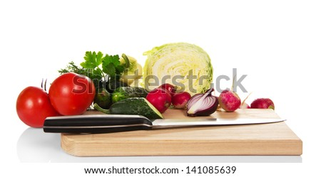 Set of vegetables and knife on the chopping board, isolated on white - stock photo