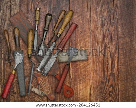 set of vintage chisels and sharpening stones, strop over wooden bench, space for your text - stock photo
