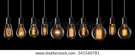 Set of vintage glowing light bulbs on black background - stock photo