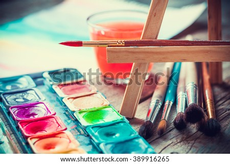 Set of watercolor paints and paintbrushes for painting closeup. Selective focus. Retro styled. - stock photo