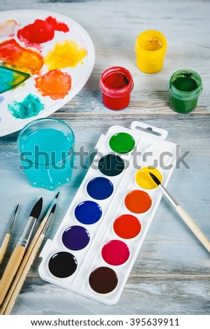 Set of watercolor paints, brushes for painting and palette on old vintage wooden background top view
