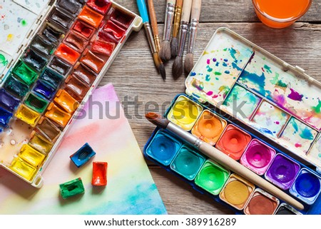 Set of watercolor paints, brushes for painting and paper sheet of painting on old wooden background. Top view. - stock photo