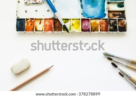 Set of watercolor paints, brushes for painting, pencil and eraser on blank white water color paper. Creation process of arts- drawing and watercolor painting. Top view. - stock photo