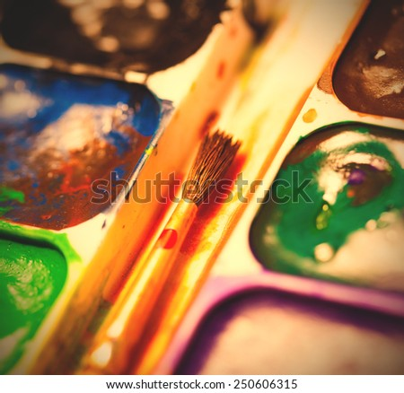 set of watercolor paints with brush, close up. shallow depth of field. instagram image retro style - stock photo