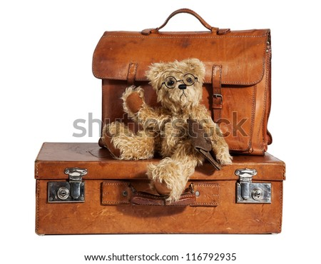 Set of Well-Traveled Vintage Suitcase and Teddy Bear isolated on white