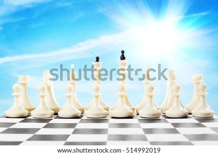 Set of white chess pieces on the chessboard against bright blue sky