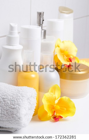 set of white cosmetic bottles with flowers over tiled wall in bathroom - stock photo
