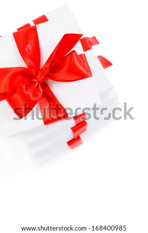 Set of white gift boxes with red ribbon and bow close up. Over white background, studio shot, with copy space.