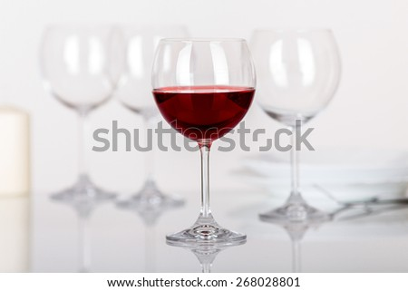 set of wine glasses with red wine on the table - stock photo