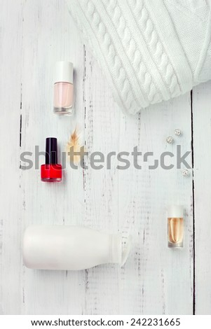 Set of winter women's accessories - wool sweater, body cream, perfume and red nail polish, on wooden floor. White collection. - stock photo