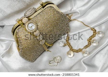 set of women's accessories on a silk background - stock photo