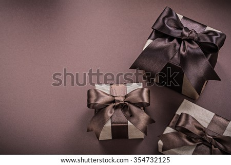 Set of wrapped present boxes on brown surface holidays concept.