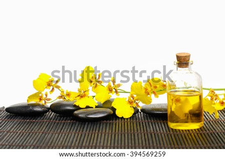 Set of yellow orchid and stones with massage oil on mat
