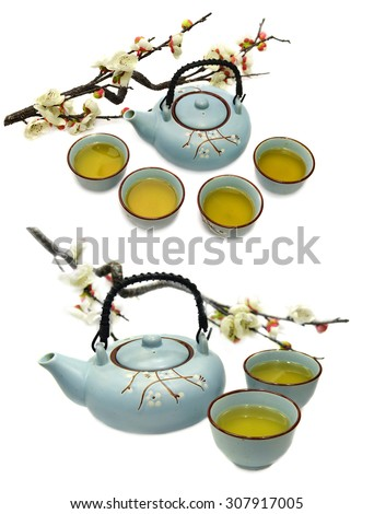 Set with blue ceramic tea pot and cups with green tea and sakura branch, kitchen objects isolated on white - stock photo