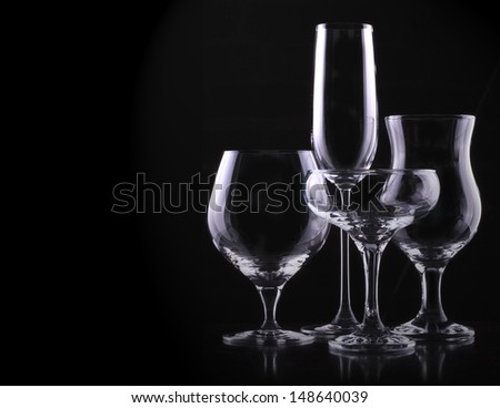 set with different empty glasses on black background - champagne,cola,cocktail,wine,brandy,whiskey,scotch,vodka,cognac