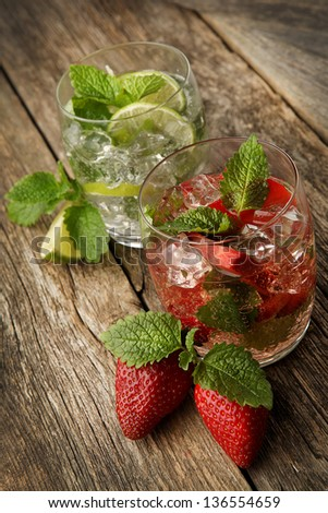 set with mojito lime and strawberry cocktails on the wooden background - stock photo