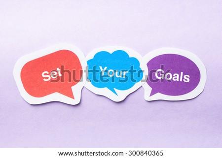 Set your goals concept paper bubbles against purple background. - stock photo
