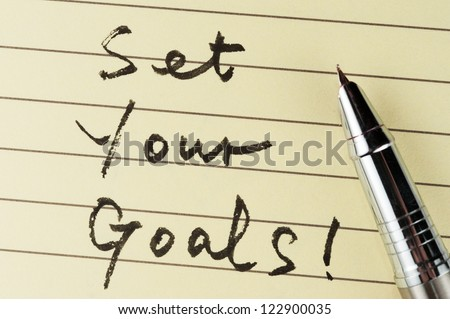 Set your goals words written on lined paper with a pen on it - stock photo