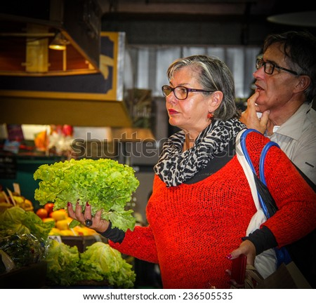 SETE, FRANCE - NOVEMBER 2: Woman buying lettuce at the market on a hot day on November 2, 2014 in Sete, France