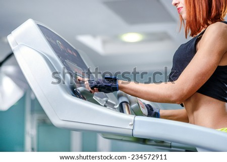 Setting employment programs. Sport and slender girl running on a treadmill. Athlete dressed in sports uniforms and running in the gym and customize simulator. - stock photo