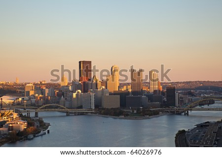 Setting sun highlights the tops of the tall buildings in downtown Pittsburgh - stock photo
