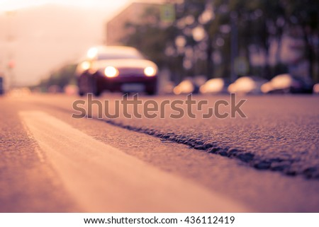 Setting sun in the suburbs, the car goes on the road. View from the level of the dividing line, image in the soft orange-purple toning - stock photo