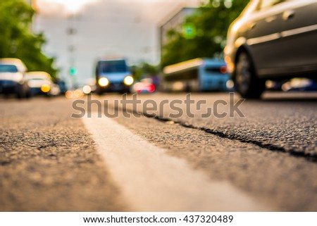 Setting sun in the suburbs, the cars driving on road. View from the level of the dividing line - stock photo