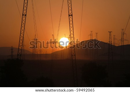 Setting Sun seen through a row of electricity pylons - stock photo