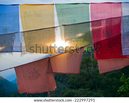Setting sun shining through colorful prayer flags with the himalayan mountains in the back - stock photo