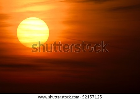 Setting sun with clouds in the sky - stock photo