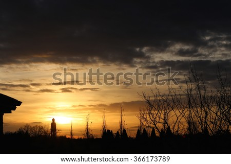 Setting sun with dark clouds on the horizon and silhouette of clock tower in the background.