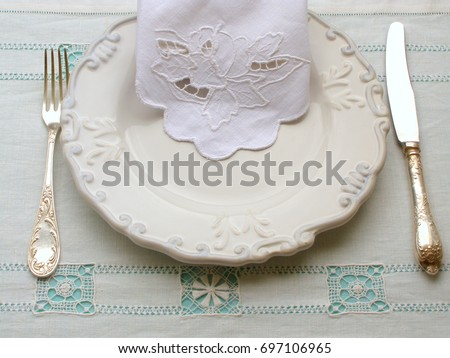 Setting The Table Over Vintage Embroidered White Linen Hemstitch Tablecloth.  Plate, Embroidered Napkin And