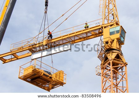 Setting up a tower crane in the construction site.  The hoist winch is lifted up. - stock photo