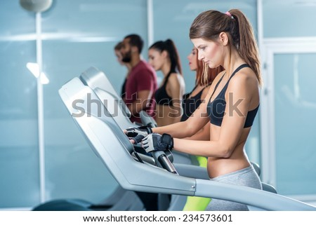 Setting up the program of sports. Sport and slender girl running on a treadmill and configures the simulator. Athlete dressed in sports uniforms and running in the gym. - stock photo
