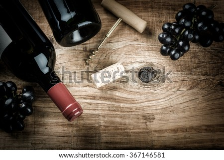 Setting with bottle of red wine, grape and corks. Wine list concept with copy space
